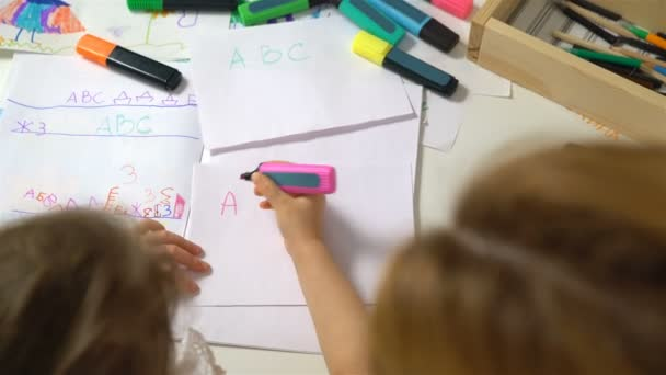 Little girl learning to write the alphabet. Dolly shot.