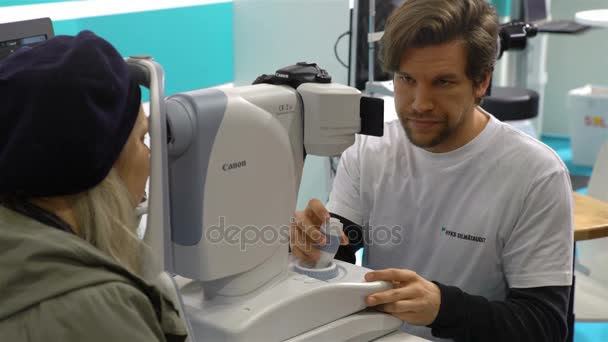 Doctor examining womans eyes with a modern digital measurement machine. Exhibition of medical equipment and services Doctor in 2017.