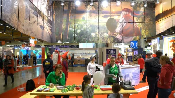 A lot of people at the pavilion of Santa Claus on a large international fair of travel agencies