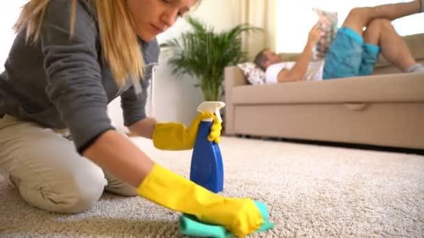 Müde Frau putzt Teppich und ihr Mann liegt mit Zeitung auf dem Sofa.