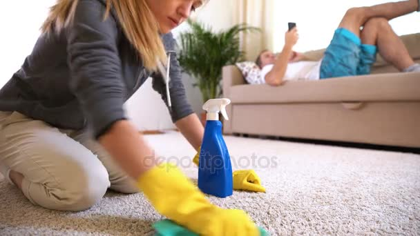 Unavená žena čistí koberec, zatímco její manžel leží na pohovce s telefonem.