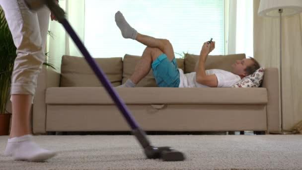 Hausfrau, Staubsaugen, Teppich und ihr Mann auf dem Sofa liegend mit smartphone