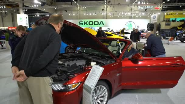Stand of new models Mustang at the auto show. Visitors examine motor of new vehi