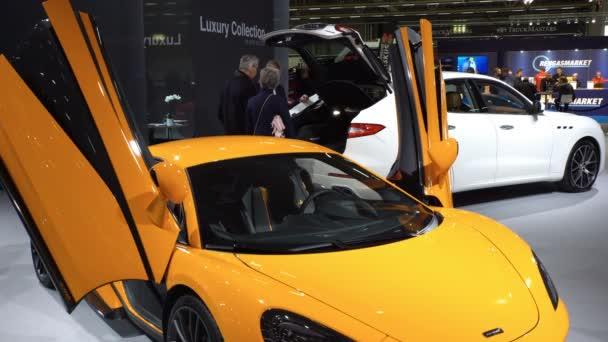 Kolekce luxusních vozů v autosalonu.