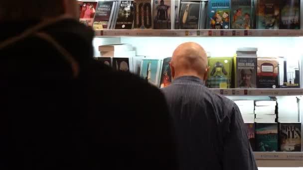 Mnozí milovníci čtení, kupující, vydavatelé a knihy na velké knižní veletrh