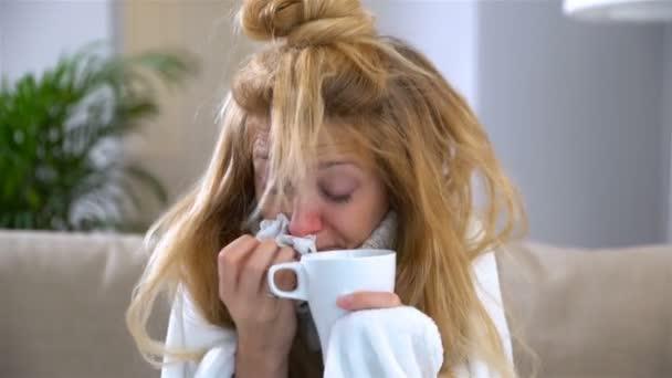 Žena s horečkou a rýma kýchne hlasitě a pije horký nápoj