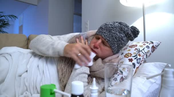 Man Wearing A Warm Cap And Scarf In A Bed Coughs And Uses Spray For Throat.