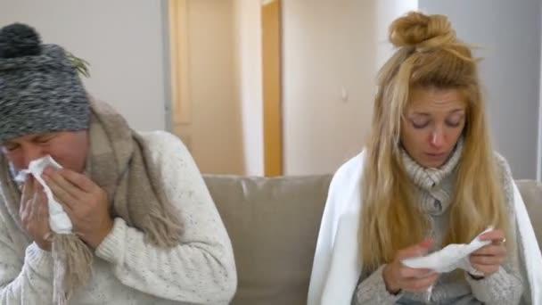 Churavějící dvojice s rýma pomocí nosních a krku sprej sedět v obývacím pokoji
