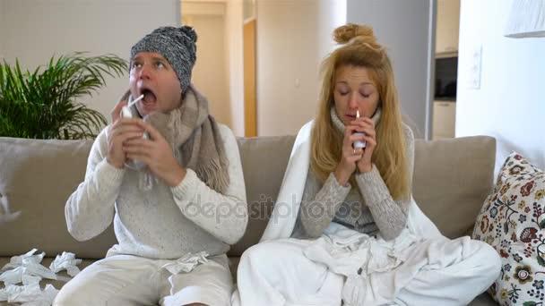 Krankes Paar mit laufender Nase mit Nasen- und Rachenspray im Wohnzimmer.