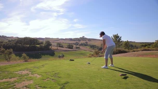 Atraktivní starší žena klepe golfový míček s Teeing hřiště v golfovém klubu
