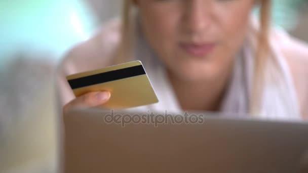 Fiatal nő használ egy arany hitelkártya Online feküdt a kanapén. Dolly lövés.