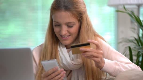 Atraktivní mladá žena dělá online nákupy používá zlatou kreditní kartu. Zpomalený pohyb