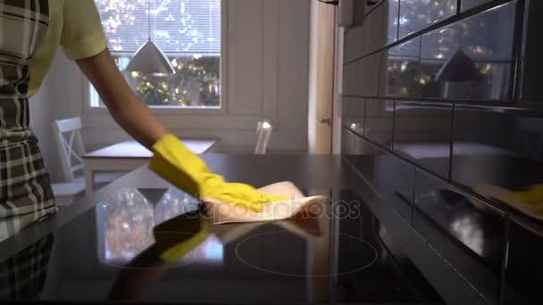 Die Hausfrau wischt die Oberfläche des Elektroherds mit einem speziellen Putztuch ab. Dolly.