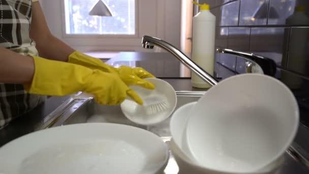 Hospodyně myje nádobí v dřezu v kuchyni. Dolly
