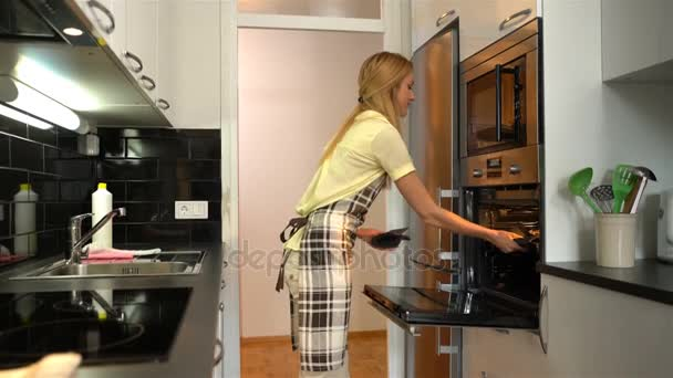 Young attractive housewife gets out of the oven delicious hot pie. Dolly
