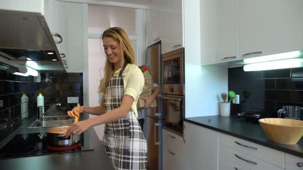 glückliches Paar in der Küche. Frau kocht, Mann bringt Tüten mit Lebensmitteln. Zeitlupe.