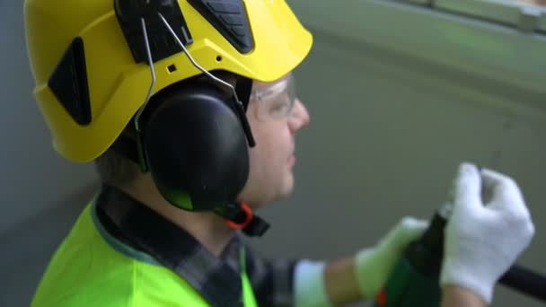 Male construction worker drilling concrete wall with a drill and smiling at the camera.
