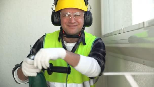 Bauarbeiter mit Bohrmaschine lächelt in die Kamera.