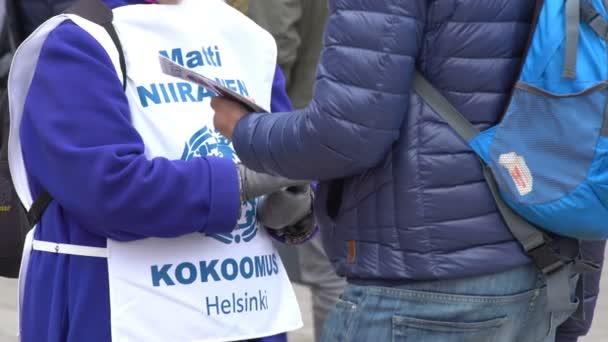 Agitatori a mano volantini per le strade di Helsinki durante la campagna elettorale