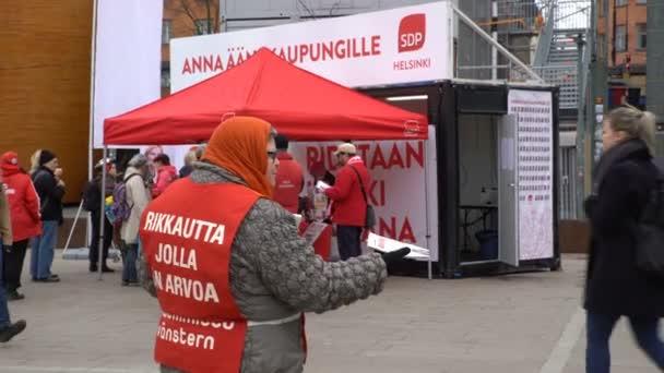 Míchadla rozdávají letáčky na ulicích Helsinky během předvolební kampaně