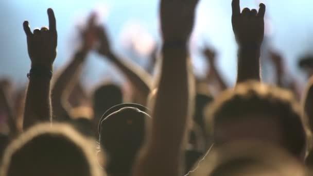 Mnoho fanoušků tleskali a mávali rukama na rockový koncert.