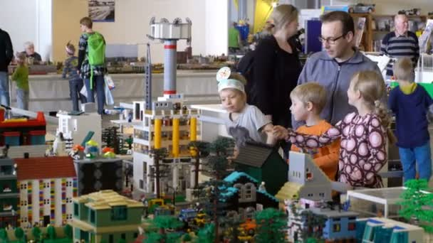Children and adults admire LEGO city.