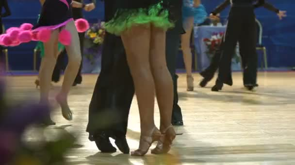 Close-up of legs of dancing couples in ballroom.