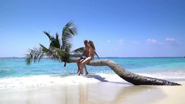 A loving couple enjoying vacation on a tropical beach. Slow Motion.