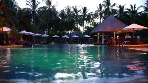 Swimming pool with a bar on a tropical resort in the evening.