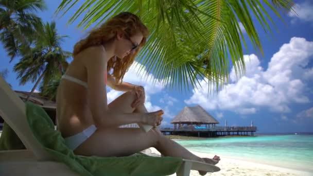 Fiatal nő, gyönyörű lábakkal használ fényvédő a trópusi tengerparton
