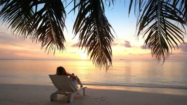 Mladá žena na tropické pláži obdivovat západ slunce.