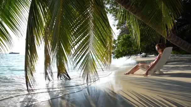 Fiatal vékony nő élvezi a nyaralás egy nyugágyon a trópusi tengerparton.