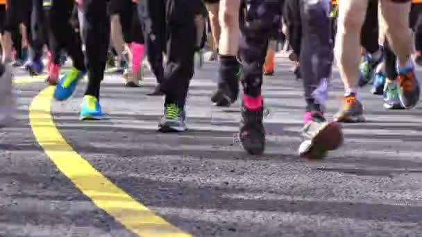 Many fans of a healthy lifestyle run city marathon. Close-up of feet.
