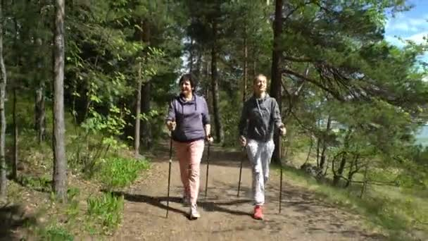 Two active women do Nordic walking in the Park. Tracking shot.