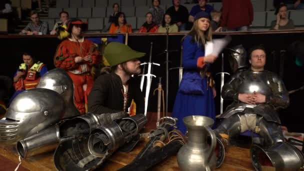 Squires, judges and knights watch jousting tournament.