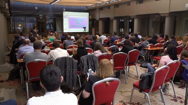 Konferenzteilnehmer hören dem Referenten zu.