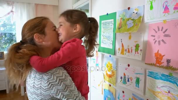 Kislány, és ő anya egyenlő óvoda ellen a falon a gyermek rajzok
