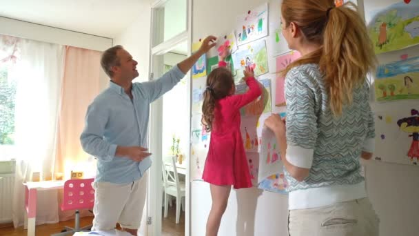 Kleines Mädchen Mit Eltern Hängen Kinder Zeichnungen An Der Wand Im  Kinderzimmer U2014 Stockvideo