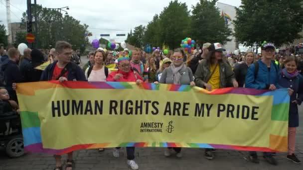 Velký duhový nápis o lidských právech v gay parade.