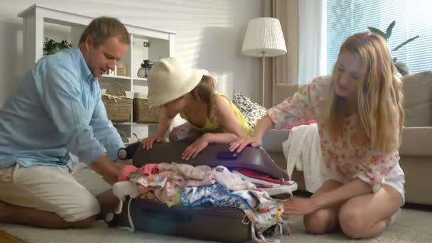 Mladá rodina s dítětem snaží uzavřít přecpaný kufr