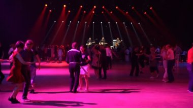 A lot of couples are dancing swing. Vintage dance in a disco with live musical accompaniment.