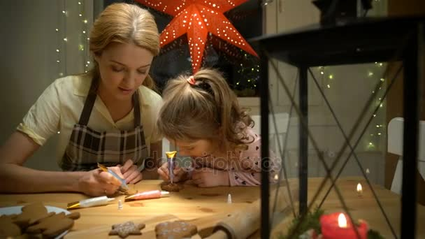 Young mother and her little daughter prepare Christmas cookies
