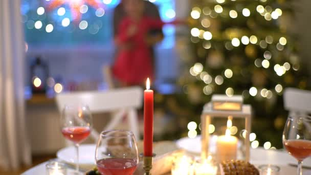 A young woman lights the candles at the Christmas table.