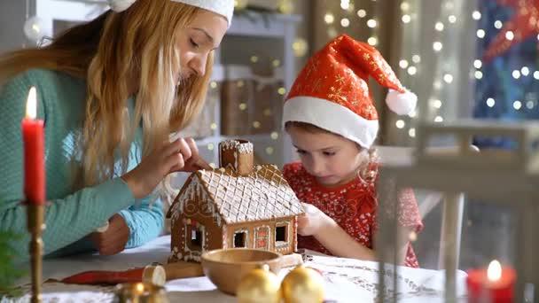 Junge Mutter und Tochter adorable in roten Hut Lebkuchenhaus gemeinsam bauen.