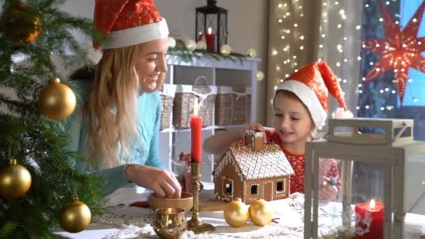 junge Mutter und entzückende Tochter mit rotem Hut bauen zusammen Lebkuchenhaus.