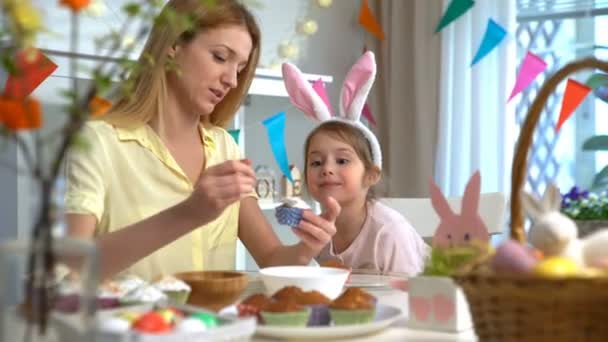 Young mother and her little daughter with rabbit ears cooking Easter cupcakes