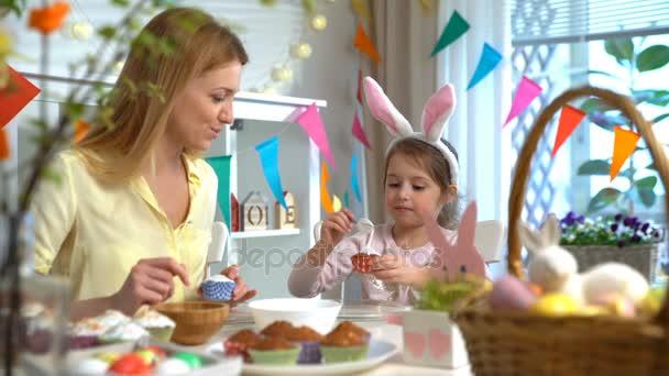 Fiatal anya és vele a kis lányom nyúl füle húsvéti cupcakes főzés