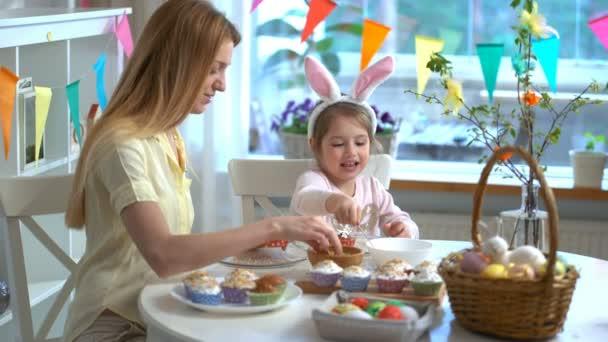 Mladá matka a její malá dcera s králičí uši vaření velikonoční košíčky