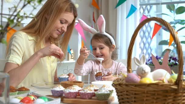 Fiatal anya és lánya visel főzés cupcakes húsvéti nyuszi füle