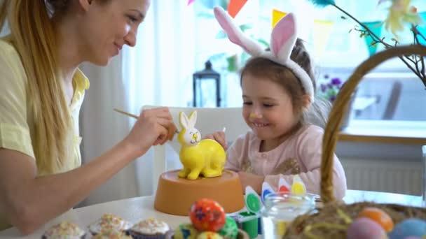 Šťastné Velikonoce matka a její malá dcera s uši zajíček Malování Velikonoční zajíček